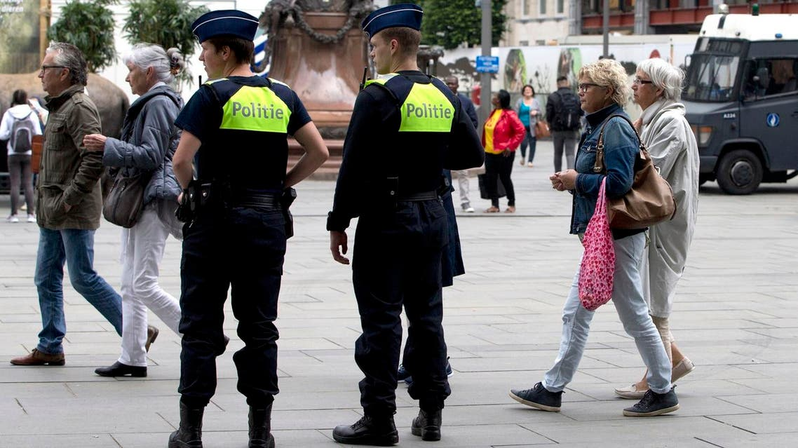 People walk by police standing guard outside the Antwerp Central train station in Antwerp, Belgium on Saturday, June 18, 2016. Police and the bomb squad unit responded to a suspect package in the Antwerp station while the Belgian federal prosecutor's office said early Saturday that homes and car ports were searched in 16 municipalities, mostly in and around Brussels in an anti-terror sweep. (AP Photo/Virginia Mayo)