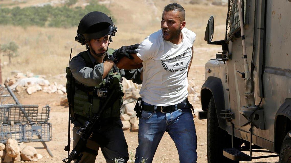 An Israeli border policeman detains a Palestinian man as Israeli troops demolish sheds belonging to Palestinians near the West Bank village of Yatta, south of Hebron June 19, 2016. REUTERS