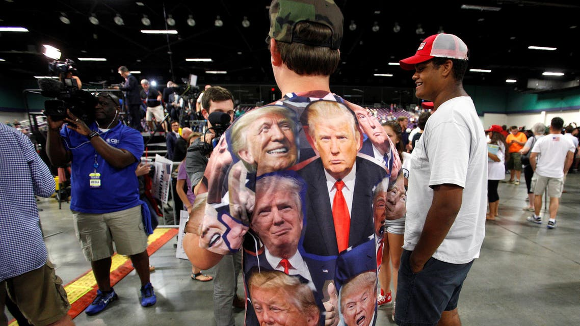 A supporter of Republican presidential candidate Donald Trump wears a shirt emblazoned with images of the politician as he is interviewed at a campaign rally in Greensboro, North Carolina on June 14, 2016. (Reuters)