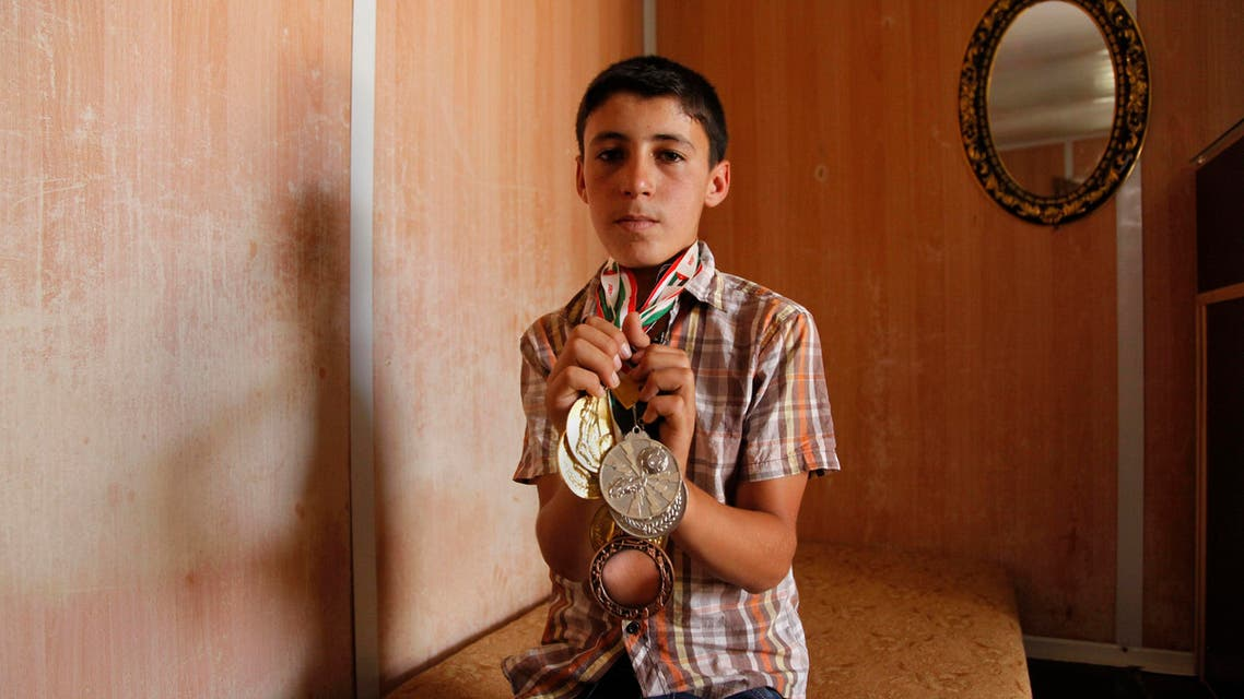 Ayman Ashara, 13, holds gold, silver and bronze medals he's earned playing football in the Zaatari refugee camp, northern Jordan, Sunday, June 19, 2016.  (AP)