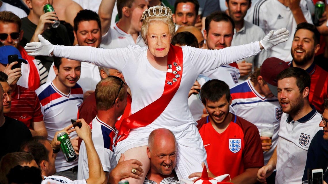 An England fan wears a mask of Queen Elizabeth II as he rides on the shoulders of his mates gathering in Saint Etienne ahead of their team's match against Slovakia. (Reuters)