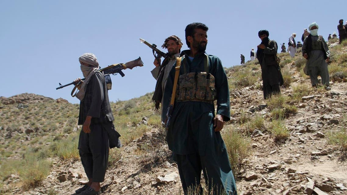 In this Friday, May 27, 2016 photo, Taliban fighters stand guard as senior leader of a breakaway faction of the Taliban Mullah Abdul Manan Niazi, not pictured, delivers a speech to his fighters, in Shindand district of Herat province, Afghanistan. In the rugged terrain of the Taliban heartland in southern Afghanistan, the fight against Kabul has become a war for control of key stretches of main roads and highways as the insurgents use a new tactic to gain ground. (AP Photos/Allauddin Khan)