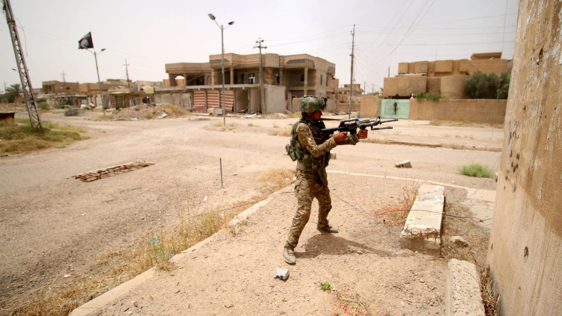 A member of the Iraqi pro-government forces patrols the al-Dhubat II (Officers) neighbourhood of Fallujah as they try to clear the city of Islamic State (IS) group fighters still holed up in the former jihadi bastion on June 19, 2016. AFP