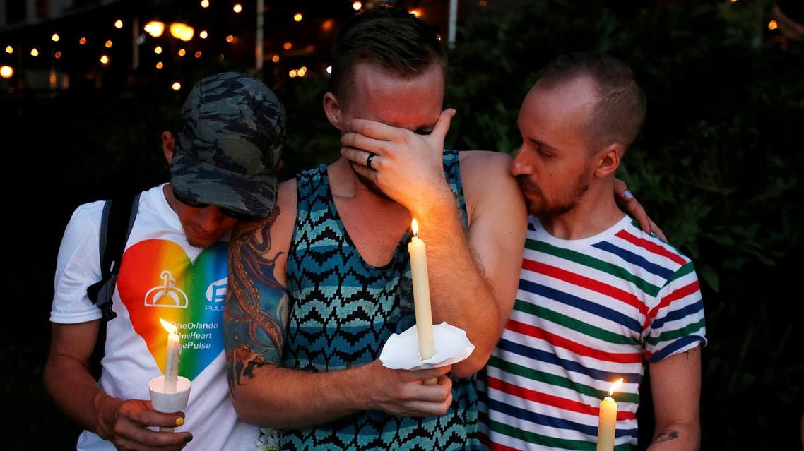 A man cries while his friends comfort him as they take part in a vigil for the Pulse night club victims following last week's shooting in Orlando, Florida, U.S., June 19, 2016. REUTERS