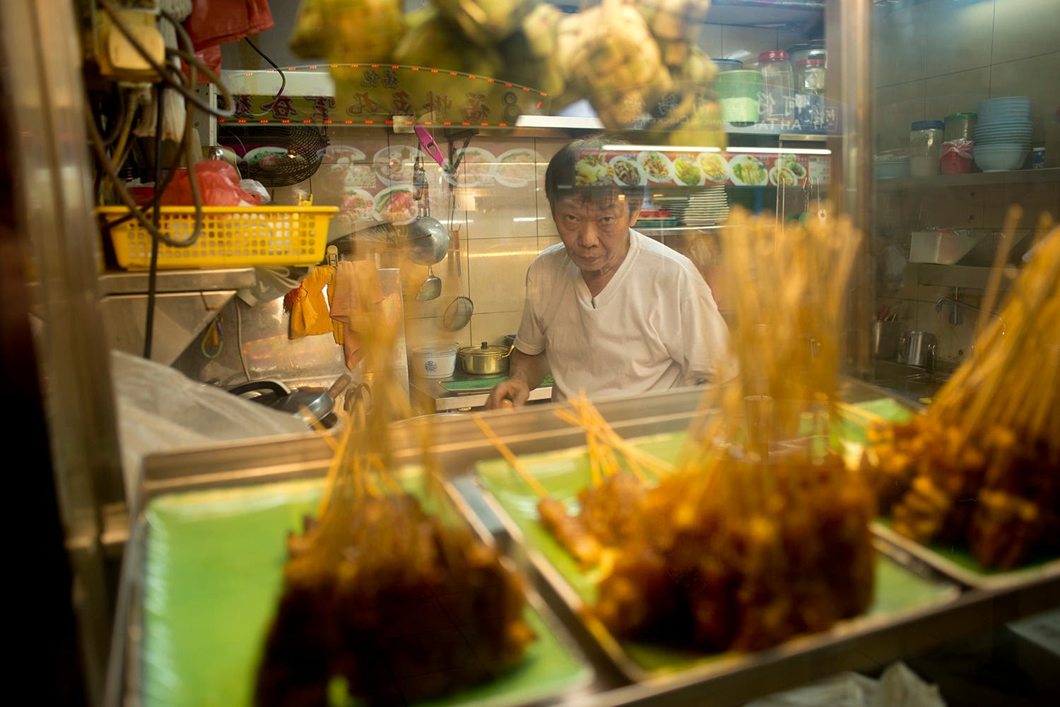 A vendor making satay looks out from his kitchen in a Singapore hawker market (Photo: Peter Harrison)