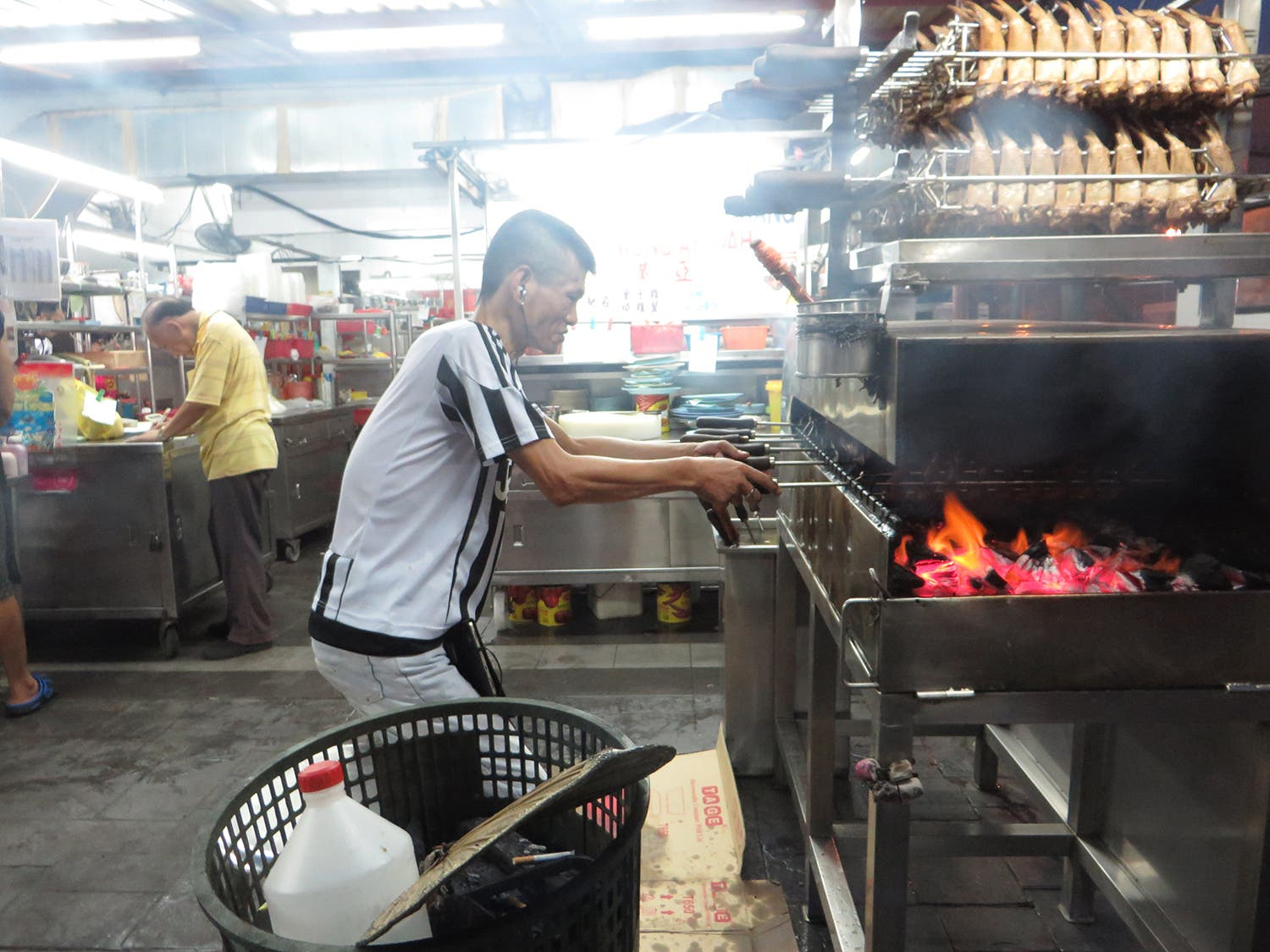 A man tends to chicken wings cooking at a Malaysian street food market (Photo: Peter Harrison)