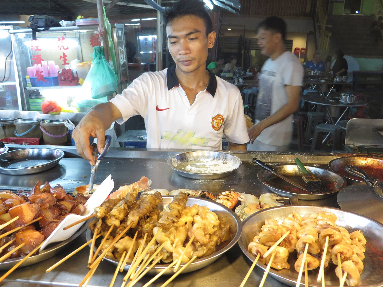 A vendor serves satay (Photo: Peter Harrison)