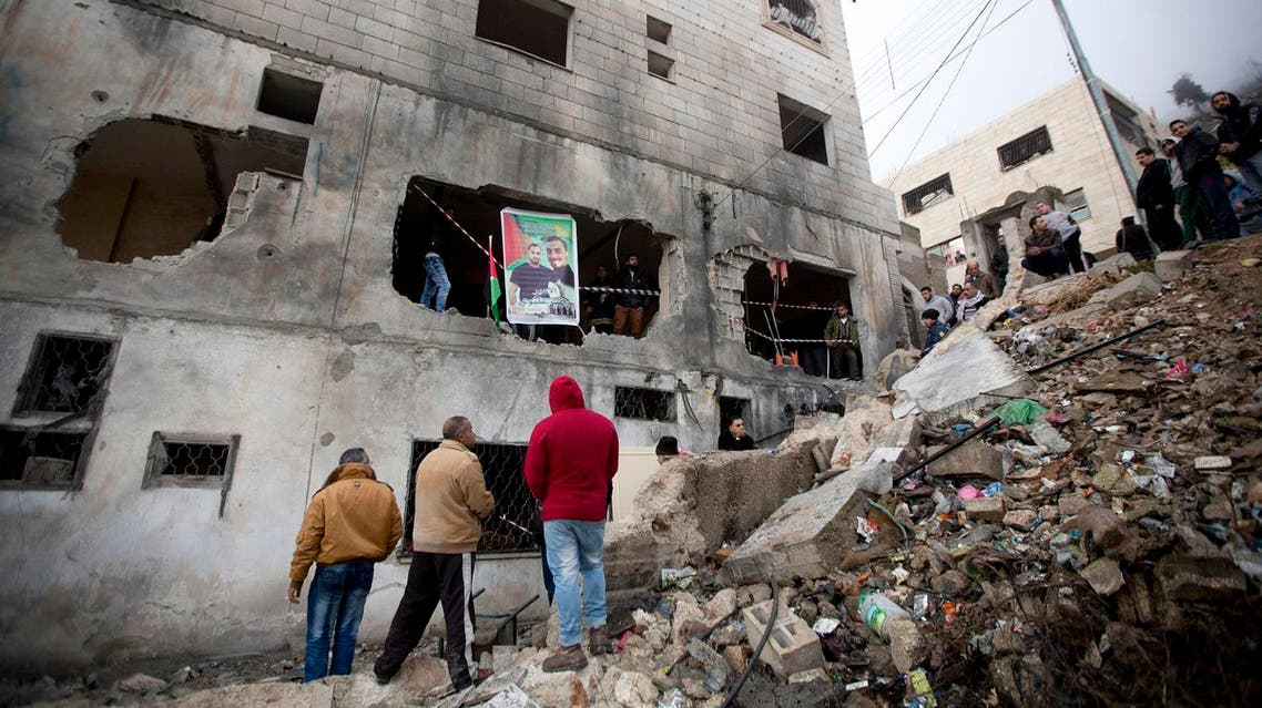Palestinians gather by a destroyed house of Raeb Ahmed Muhammad Alivi that was demolished by the Israeli army in the West Bank city of Nablus, Thursday, Dec. 3, 2015 (Photo: AP)