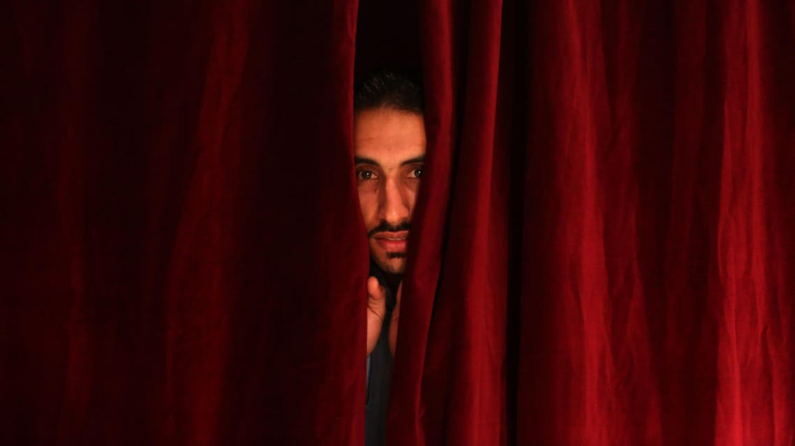 "An inmate of Lebanon's Roumieh main prison peers through the prison theater during the rehearsal of a play dubbed ""Johar...Up in the air"" on May 5, 2016. (AFP)"