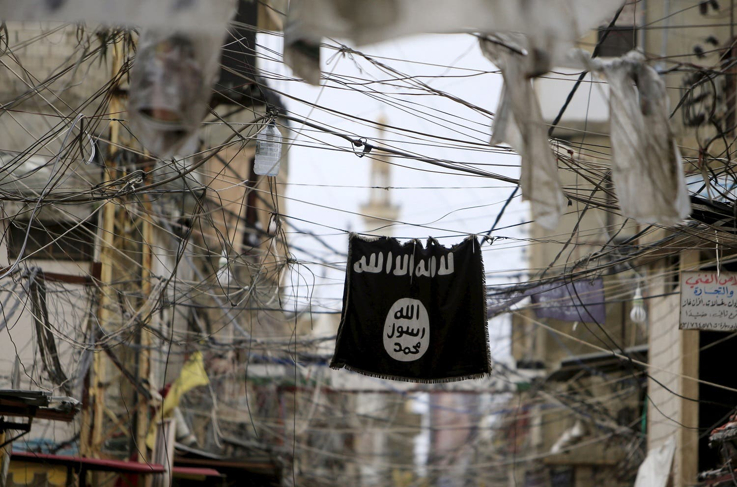 An Islamic State flag hangs amid electric wires over a street in Ain al-Hilweh Palestinian refugee camp, near the port-city of Sidon, southern Lebanon January 19, 2016. REUTERS