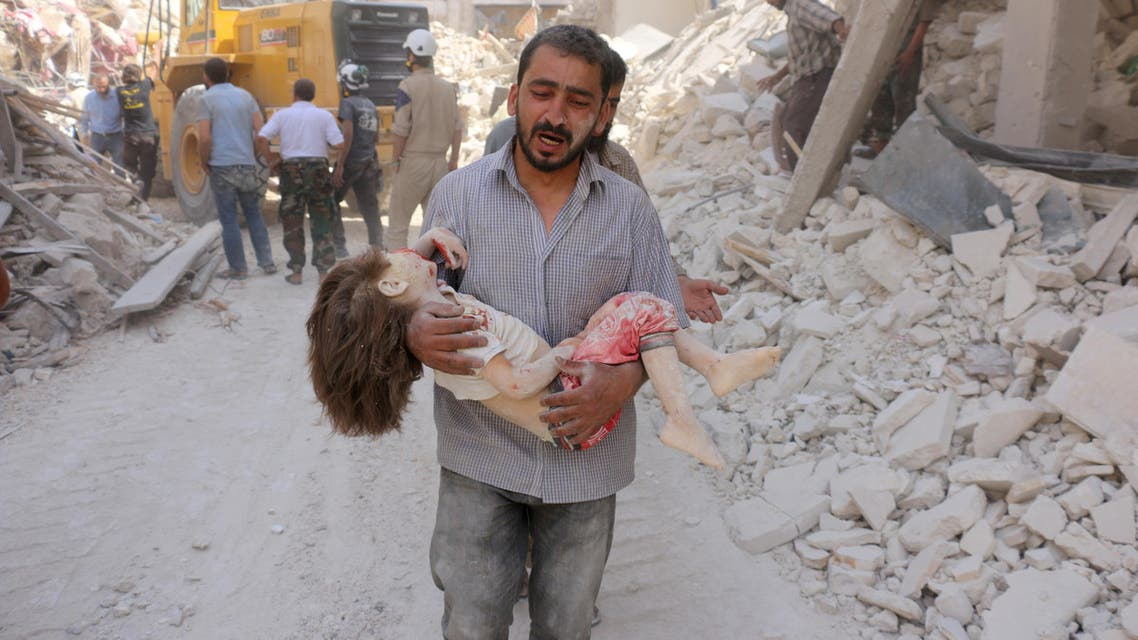 A Syrian man carries the body of a child following a reported Syrian government forces bombing at the Tariq al-Bab neighbourhood in the rebel-held area of the northern city of Aleppo on June 20, 2016.