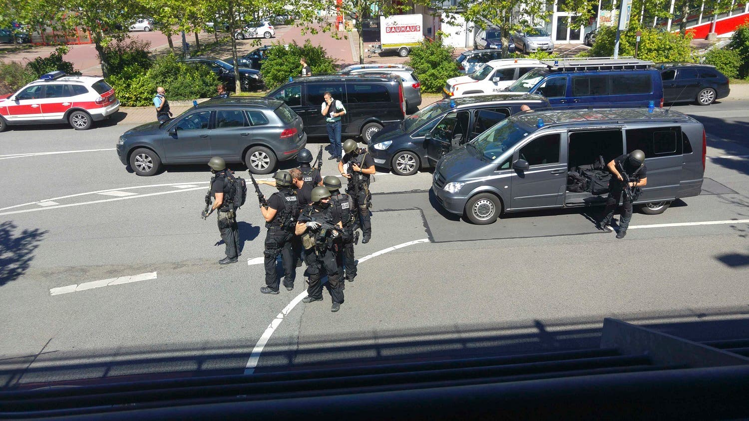 German special police leave their cars after a masked man with a gun and ammunition belt opened fire in a cinema complex in the small western town of Viernheim, near Frankfurt, Germany, June 23, 2016. REUTERS/Handout/Rhein-Neckar-Fernsehen