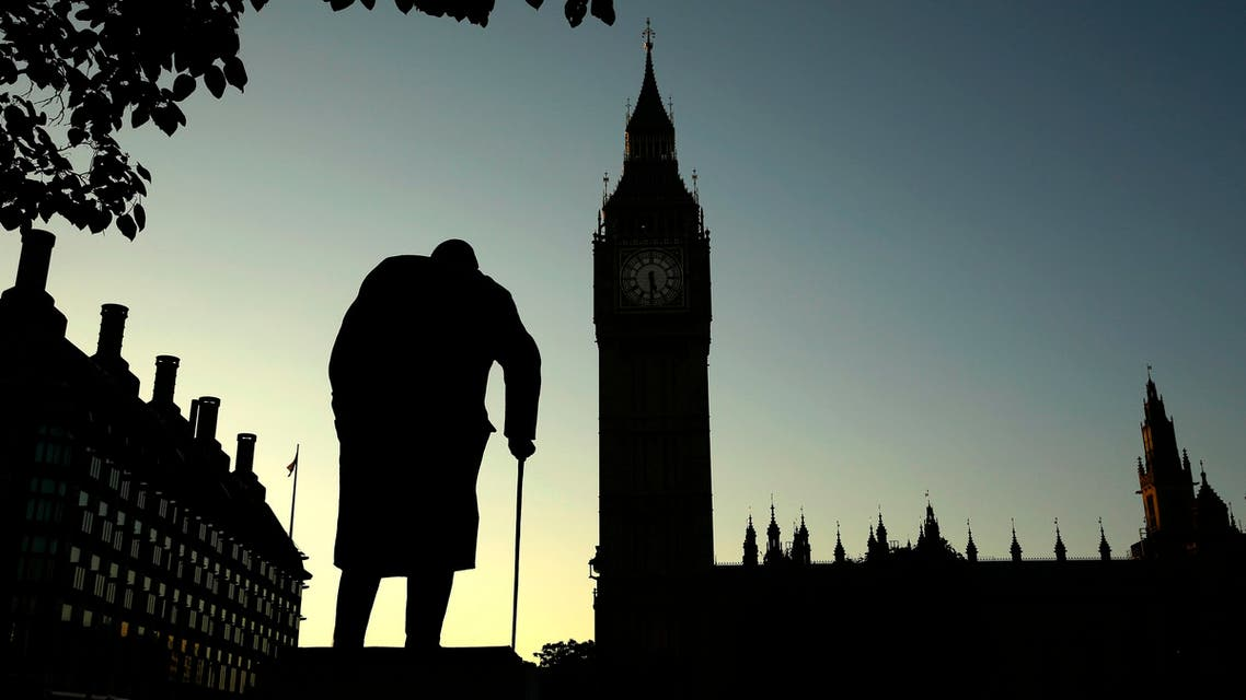 A statue of Winston Churchill is silhouetted against the Houses of Parliament and the early morning sky in London, Friday, June 24, 2016. (AP)