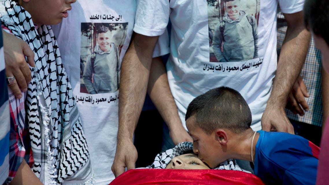 A Palestinian boy kisses the body Mahmoud Badran, 15, who was killed when the car he was traveling in was hit by Israeli army fire, during his funeral in the West Bank village of Beit Ur al-Tahta, near Ramallah, Thursday, June 23, 2016. AP