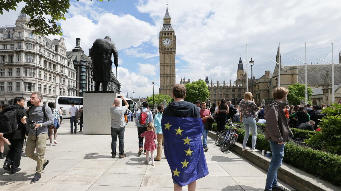 A demonstrator wrapped in the EU flag takes part in a protest opposing Britain's exit from the European Union in Parliament Square following yesterday's EU referendum result, London, Saturday, June 25, 2016. Britain voted to leave the European Union after a bitterly divisive referendum campaign. (AP Photo/Tim Ireland)