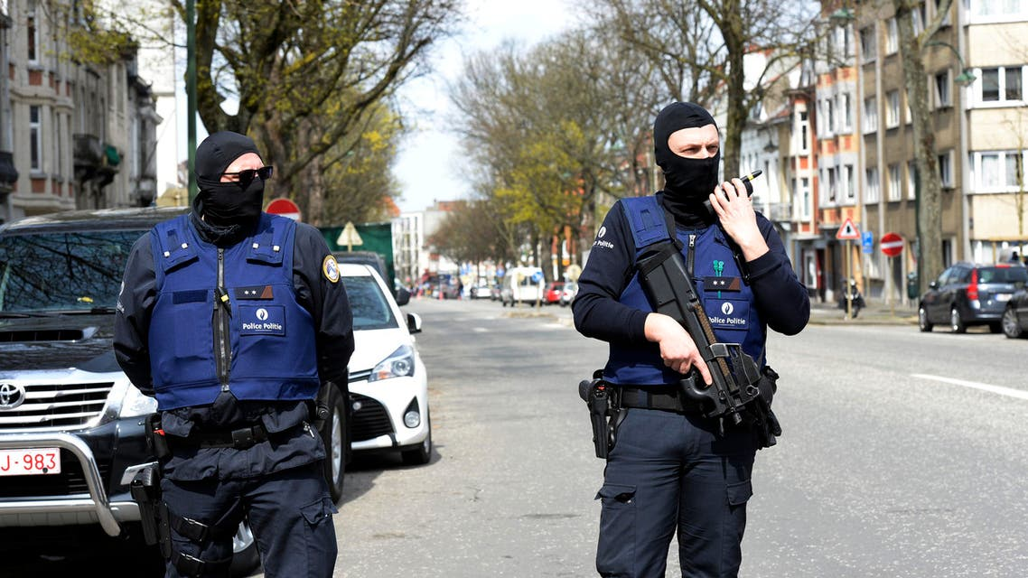 Belgian police officers stand guard in a street in Etterbeek while their colleagues search a warehouse in relation with terrorists arrests in Belgium, on April 09, 2016. A sixth person was arrested during raids on April 8, 2016 over the Brussels airport and metro bombings which netted top Paris attacks suspect Mohamed Abrini, the Belgian prosecutor's office said. THIERRY CHARLIER / AFP