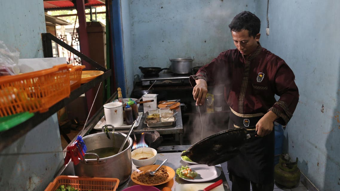 "In this Monday, May 16, 2016 photo, Mahmudi Haryono, 40, who is also known by his militant alias ""Yusuf Adirama"" cooks in the kitchen of his restaurant in Solo, Central Java, Indonesia. (ap)"