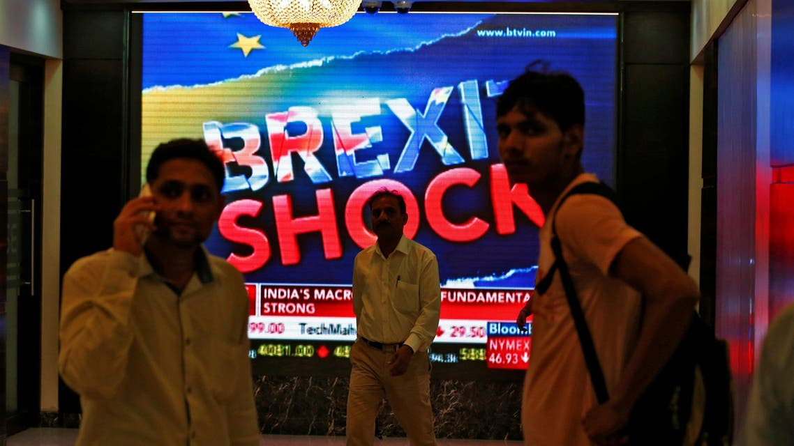 People stand past a a screen displaying news of markets update inside the Bombay Stock Exchange (BSE) building in Mumbai, India, June 24, 2016. (Reuters)