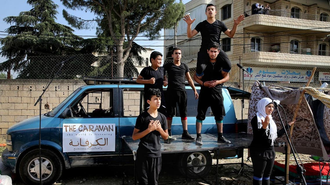 In this photo taken on Tuesday June 21, 2016, Syrian refugee actors part of The Caravan, a street performance project touring Lebanon, perform at an open market in the eastern town of Saadnayel, in Bekaa valley, Lebanon. (AP