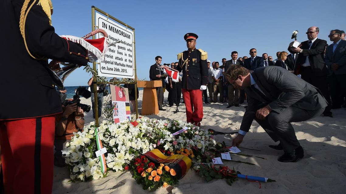 Britain's Foreign Office junior minister, Tobias Ellwood, lays a flower on the beach on June 26, 2016, during a ceremony in memory of those killed a year ago by a jihadist gunman in front of the Riu Imperial Marhaba Hotel in Port el Kantaoui, on the outskirts of Sousse south of the capital Tunis. Tourists fled in horror on June 26, 2015 as a Tunisian gunman pulled a Kalashnikov rifle from inside a furled beach umbrella and went on a shooting spree outside the five-star hotel. 30 Britons were among 38 foreign holidaymakers killed in the attack. FETHI BELAID / AFP