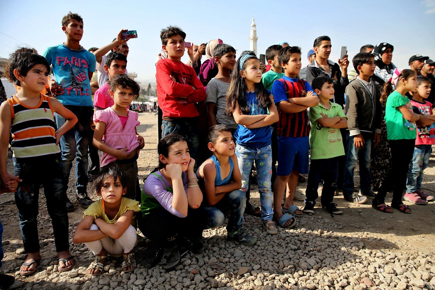 In this photo taken on Tuesday June 21, 2016, Syrian and Lebanese children watch a performance by The Caravan, a street performance project touring Lebanon, at an open market in the eastern town of Saadnayel, in Bekaa valley, Lebanon. The Caravan plans to tour Lebanon over the next six weeks, telling stories recorded and acted by Syrian refugees. And the range of reactions at the Saadnayel market is precisely what the directors of the project anticipated, even desired. Five years since the war in Syria, the influx has not stopped and Lebanese and Syrians alike are grappling to deal with the new reality in the absence of a political resolution. (AP)