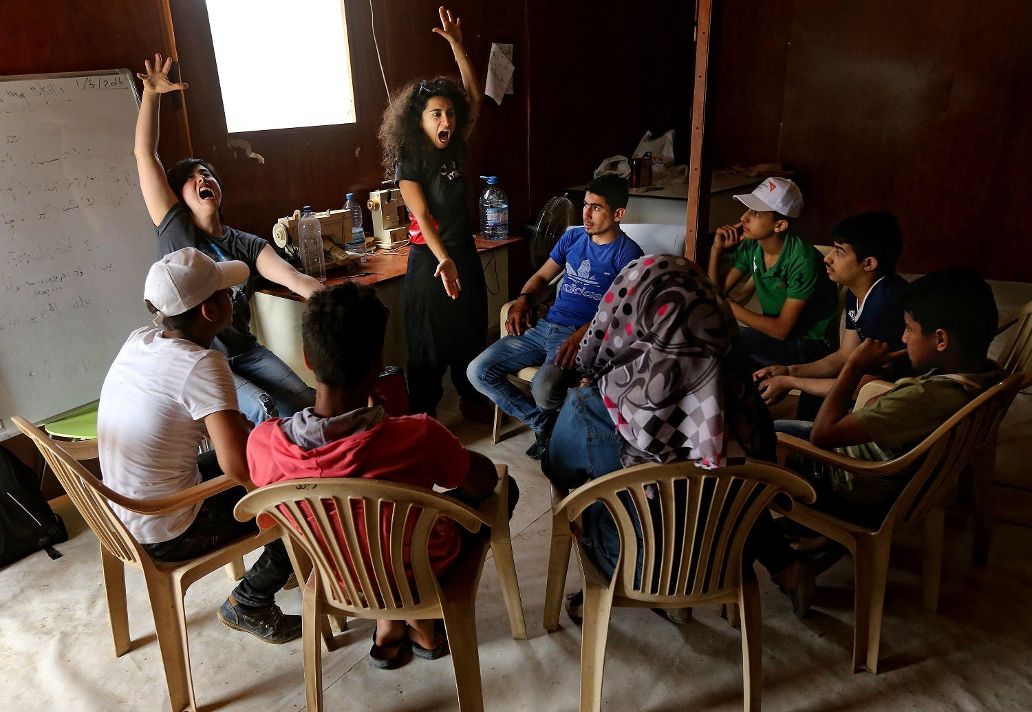 In this picture taken on Tuesday May 3, 2016, Sabine Choucair, Lebanese artistic director of The Caravan, center, and her co-director Ailin Conant, left, train Syrian refugee actors during a rehearsal performance, at an informal refugee camp, in the eastern town of Bar Elias, in Bekaa valley, Lebanon. The Caravan, a street performance project that plans to tour Lebanon over the next six weeks, is a collection of stories told, recorded and acted by Syrian refugees. And the range of reactions at the Saadnayel market is precisely what the directors of the project anticipated, even desired. Five years since the war in Syria, the influx has not stopped and Lebanese and Syrians alike are grappling to deal with the new reality in the absence of a political resolution. (AP