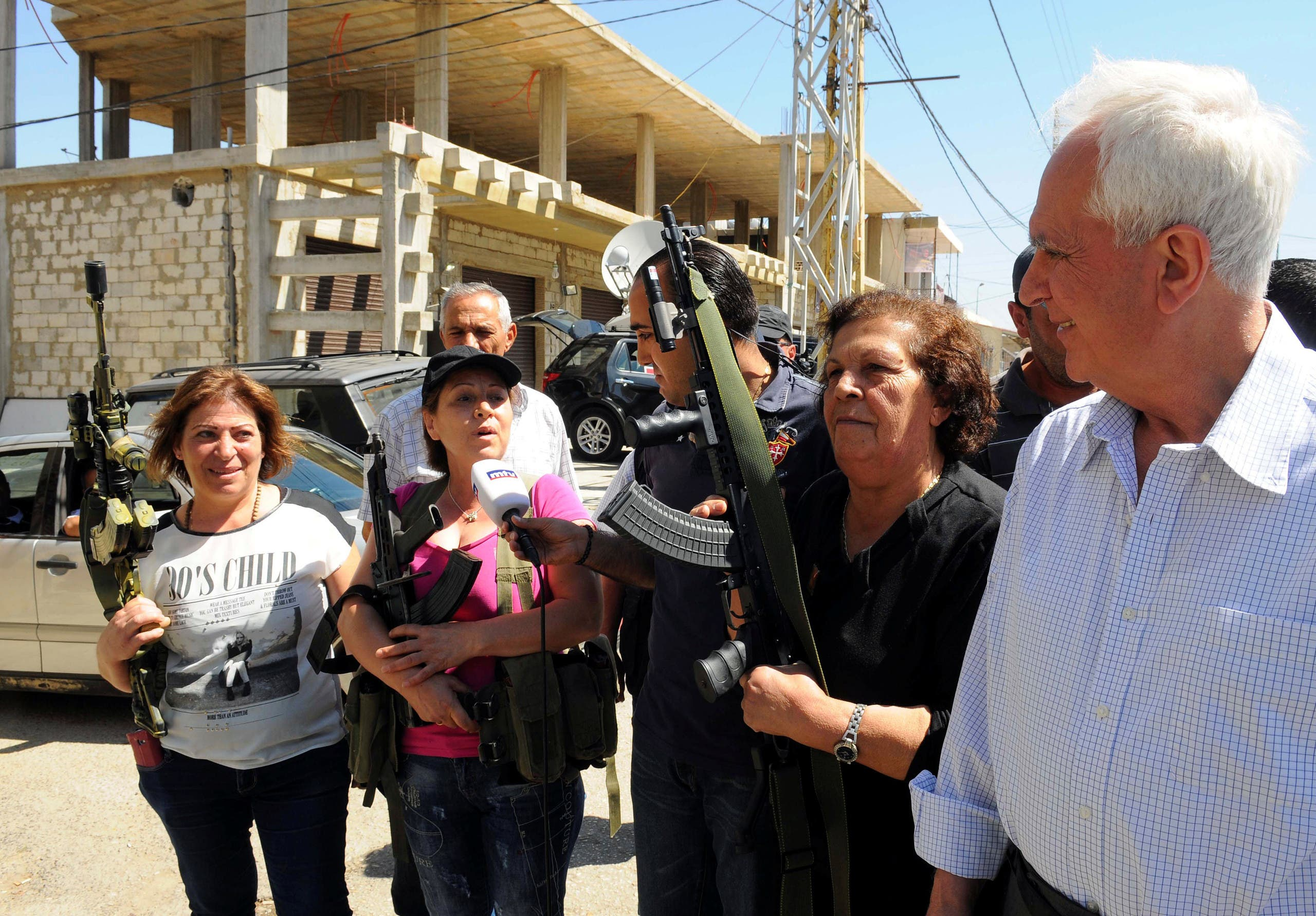 Member of the Syrian Social Nationalist Party and Lebanese MP Marwan Fares stands with women who are posing with guns and talking to journalists in the Christian village of Qaa, in the Bekaa valley, Lebanon June 28, 2016. (Reuters)