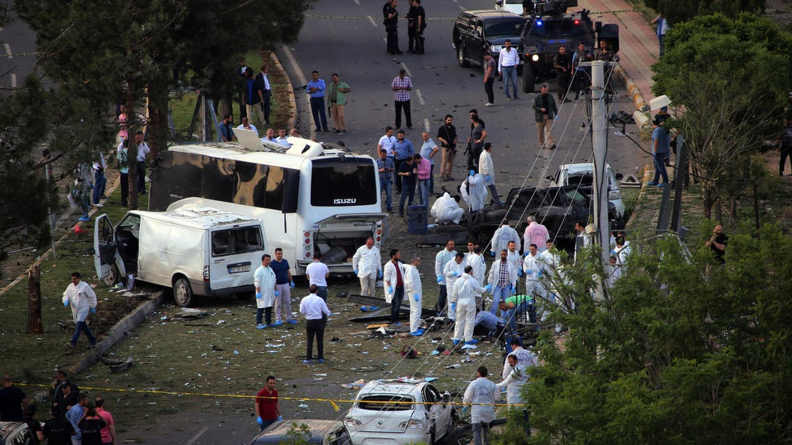 Security officers and medics work at the explosion site after a car bomb struck a bus in Diyarbakir, Turkey, Tuesday, May 10, 2016. AP
