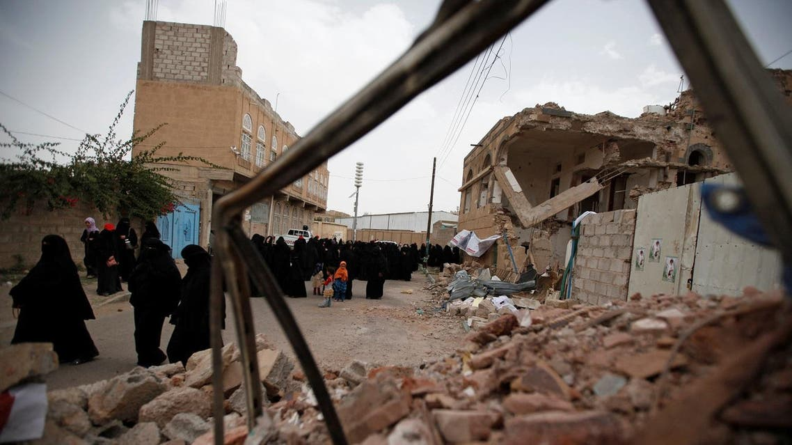 Women walk past destroyed houses during a vigil marking one year since a Saudi-led air strike on a residential area in Sanaa, Yemen June 21, 2016. REUTERS