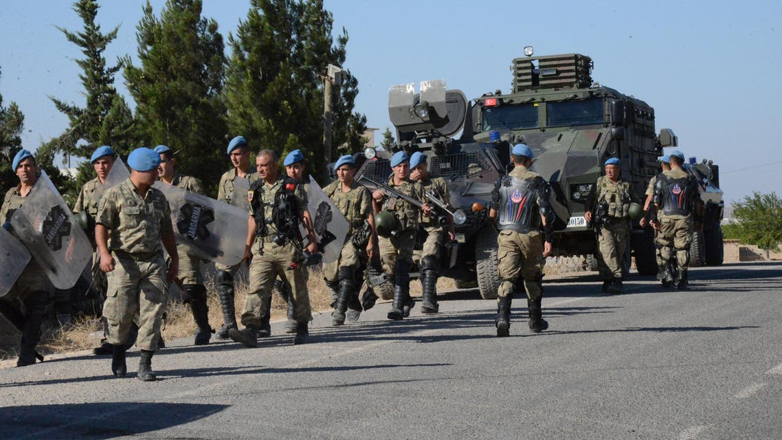 Turkish soldiers walk to their position on the Turkish side of the border in Suruc, Turkey, Friday, June 26, 2015, near the Syrian town of Ayn al-Arab or Kobani. AP