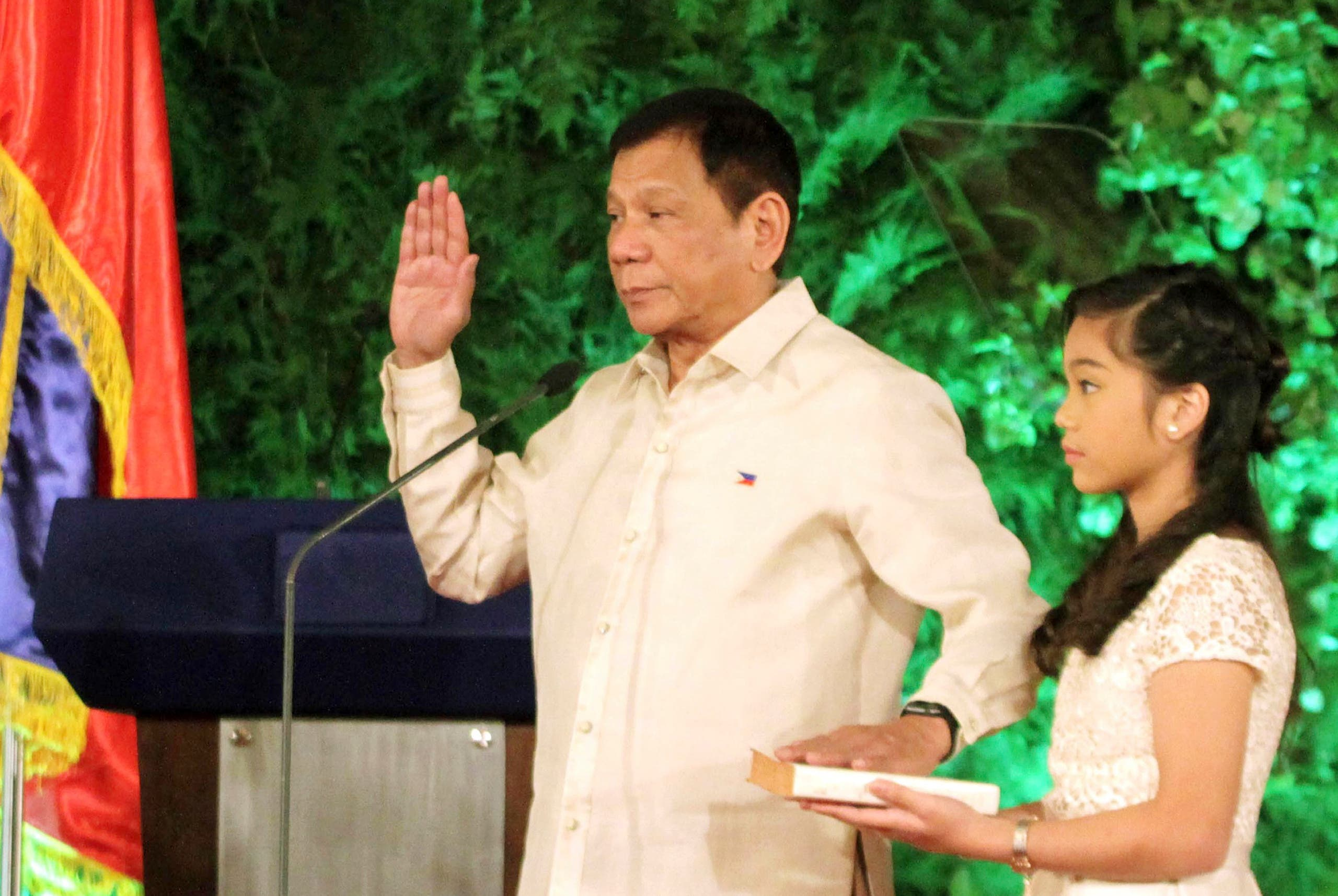 The new Philippine President, Rodrigo Duterte, takes the oath as his daughter Veronica holds the Bible during the inauguration ceremony in Malacanang Palace Thursday, June 30, 2016 in Manila, Philippines (AP)