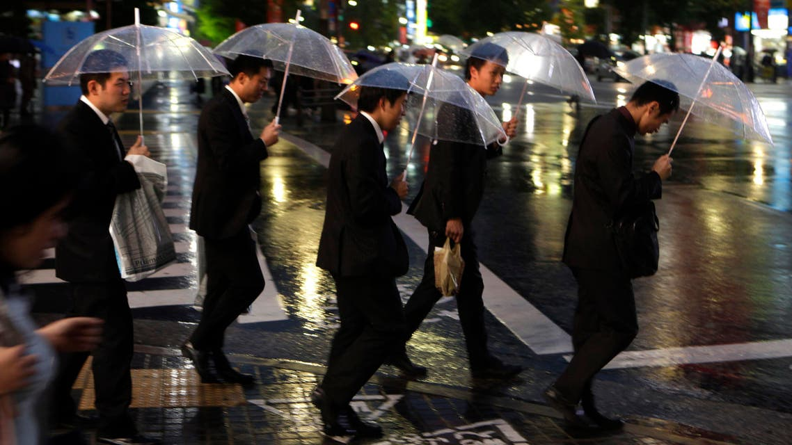 Japanese salarymen cross a street in Tokyo Monday, Nov. 15, 2010. (AP)