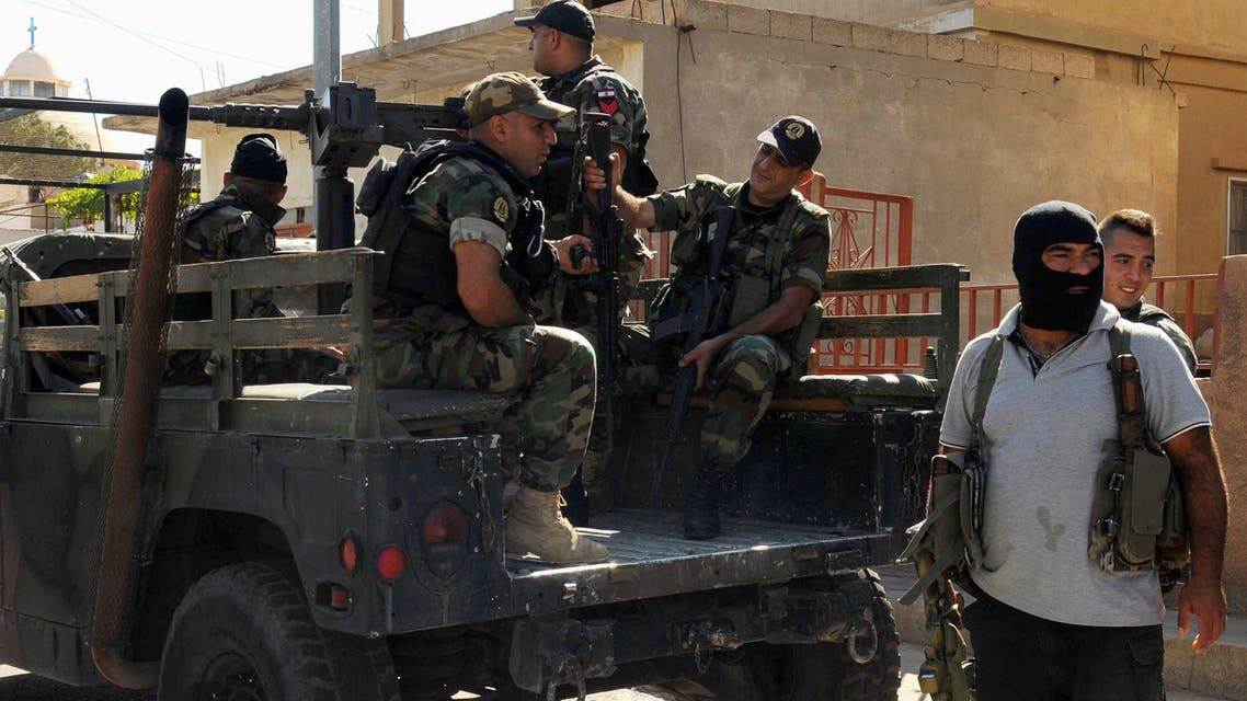 An armed resident of the Christian village of Qaa stands guard with Lebanese army soldiers near the site where suicide bomb attacks took place, in the Bekaa valley, Lebanon June 28, 2016. (Reuters)