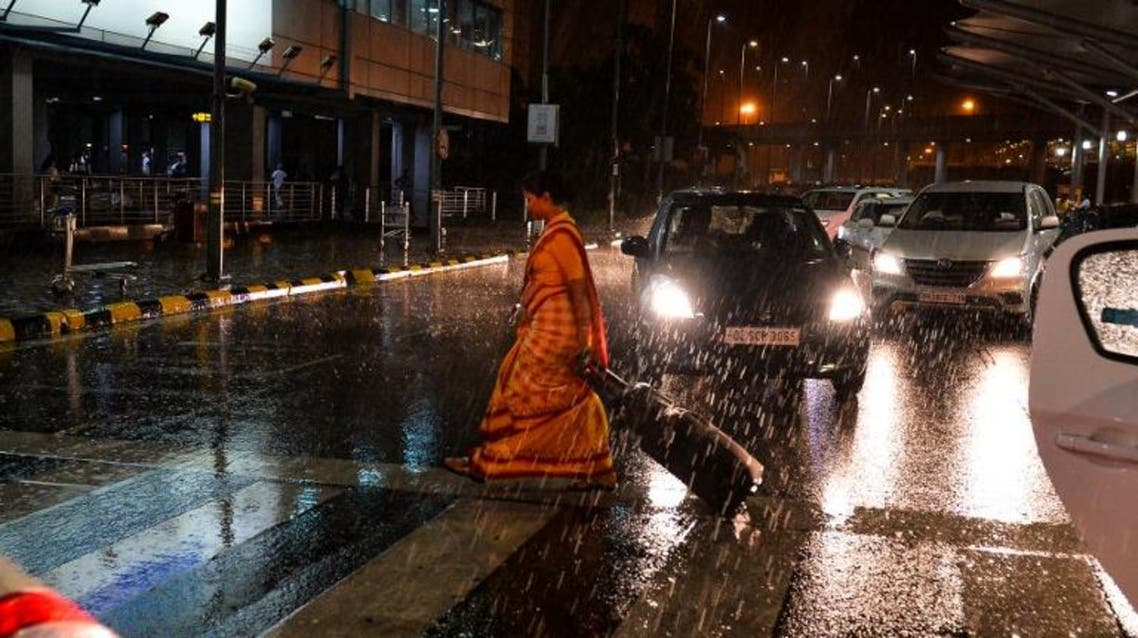 An Indian traveller crosses a road at the Delhi International Airport during heavy rain in New Delhi on early June 28, 2016. AFP