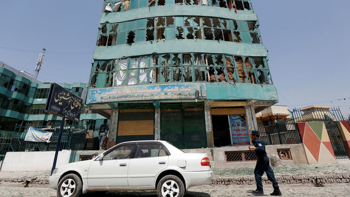 An Afghan policeman walks past a damaged building after a suicide attack in Jalalabad city, Afghanistan July 2, 2016. REUTERS