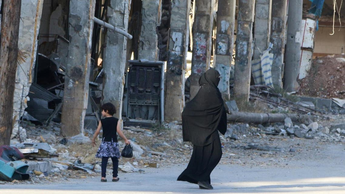 Residents walk past damaged buildings in the rebel held area of Aleppo's Bab al-Hadeed district, Syria, June 27, 2016. Picture taken June 27, 2016. REUTERS