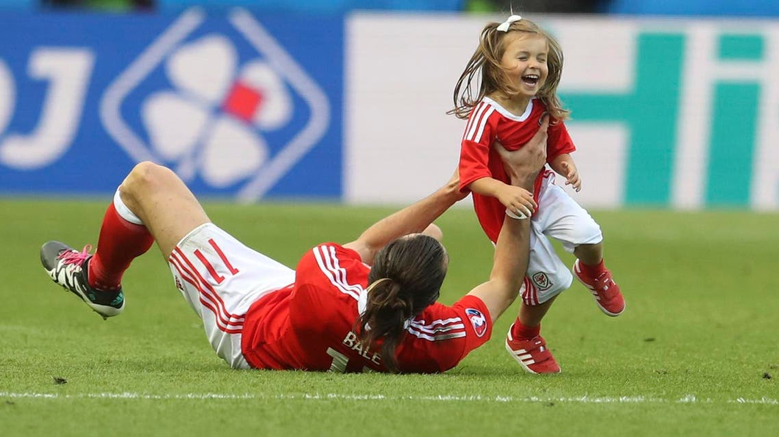 Wales' Gareth Bale celebrates with his daughter Alba after winning the Euro 2016 round of 16 soccer match between Wales and Northern Ireland, at the Parc des Princes stadium in Paris, Saturday, June 25, 2016. Wales beat Northern Ireland 1-0. (AP Photo/Petr David Josek)