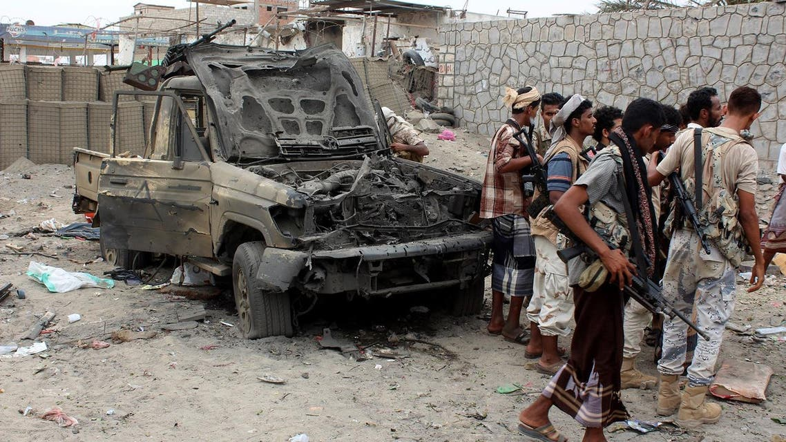 Armed Yemeni men stand next to destroyed vehicles after Yemeni government forces supported by a Saudi-led coalition recaptured an army headquarters near Aden airport from suspected militant after an hours-long firefight on July 6, 2016 in the southern city (Photo: AFP)