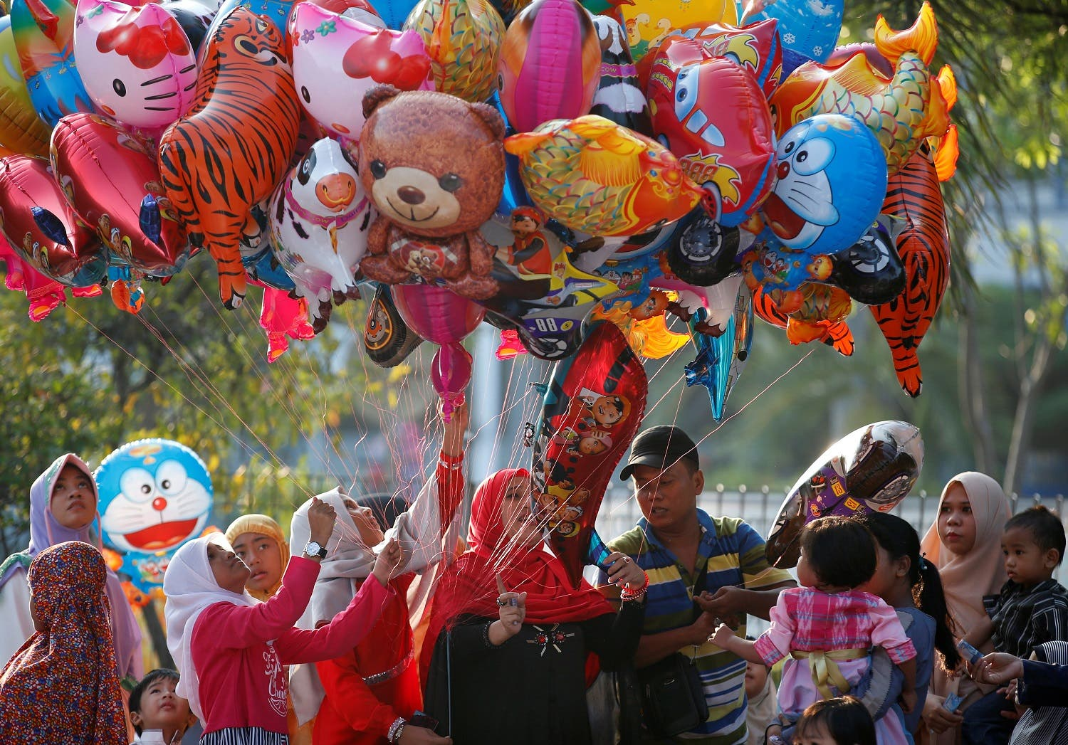 Muslims children buy balloons after attending Eid al-Fitr prayers to mark the end of the holy fasting month of Ramadan at Sunda Kelapa port in Jakarta, Indonesia July 6, 2016. REUTERS