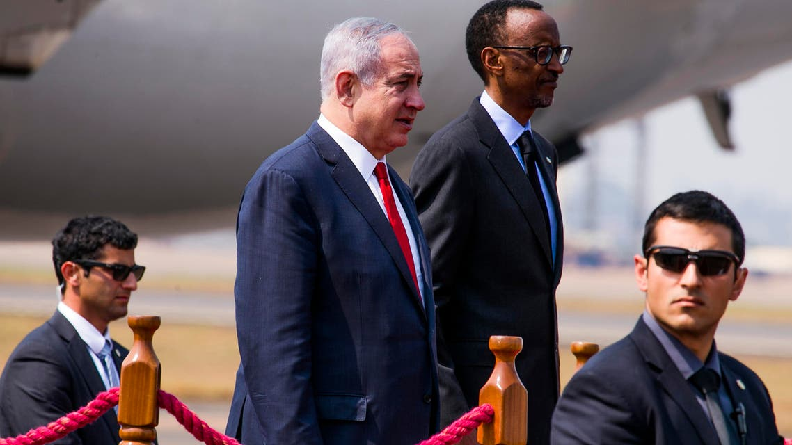 Israeli Prime Minister Benjamin Netanyahu stands (L) next to Rwanda's President Paul Kagame (R) at the airport in Kigali on July 6, 2016.