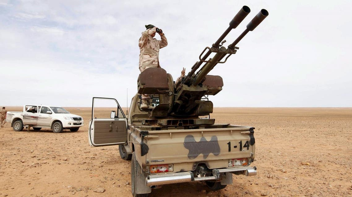 A Libyan soldier looks through binoculars at Wadi Bey, where troops are manning outposts, west of the Islamic State-controlled city of Sirte, February 23, 2016. REUTERS