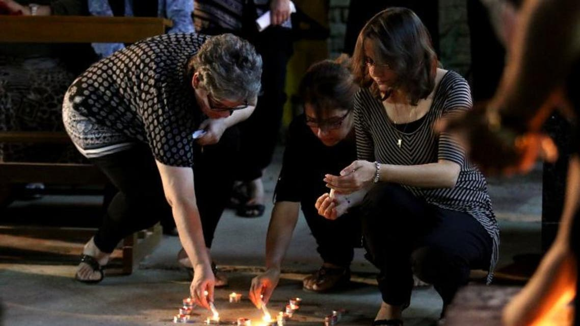 Iraqi Christians light candles during a mass in the memory of the victims of a suicide bombing, that ripped through Baghdad's busy shopping district of Karrada, on July 6, 2016. AFP