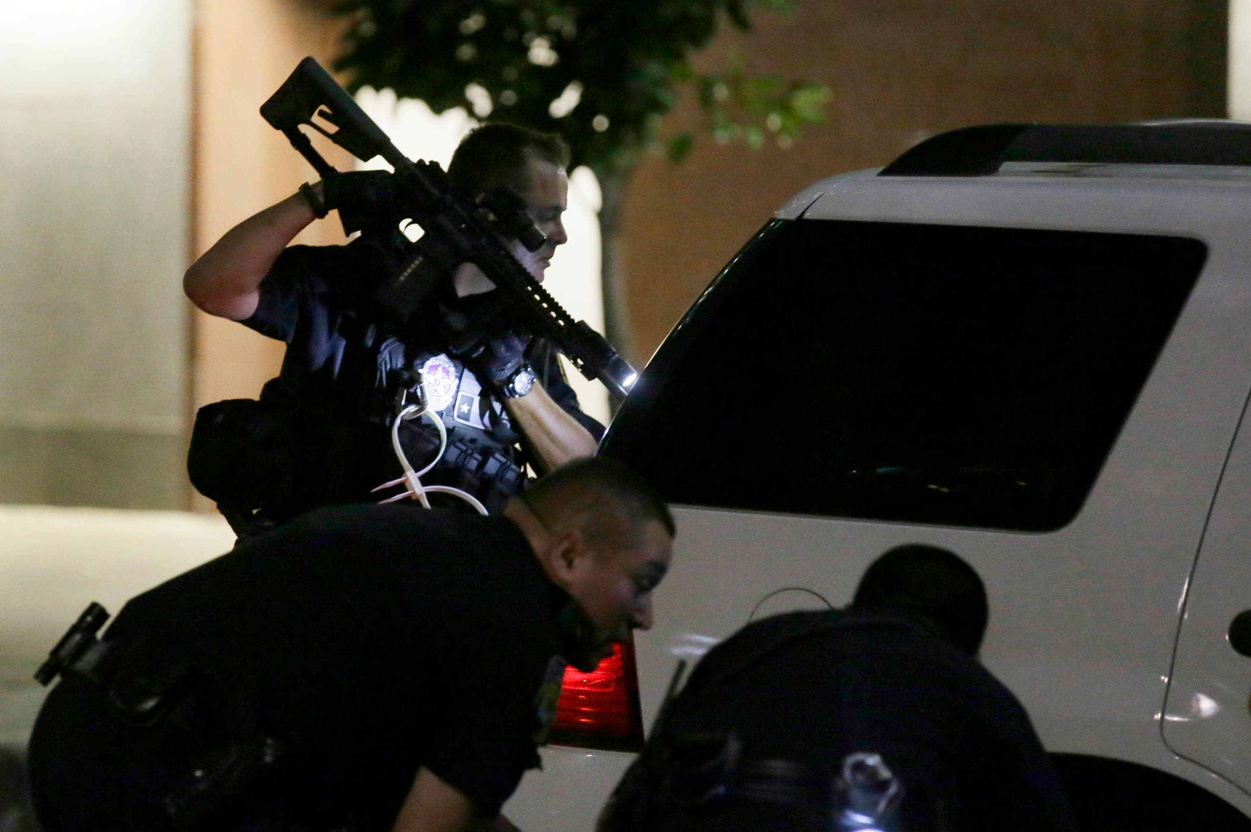 Dallas police check a car after detaining a driver in downtown Dallas, Thursday, July 7, 2016. Several police officers were shot by snipers, police said; some of the officers were killed. (AP)