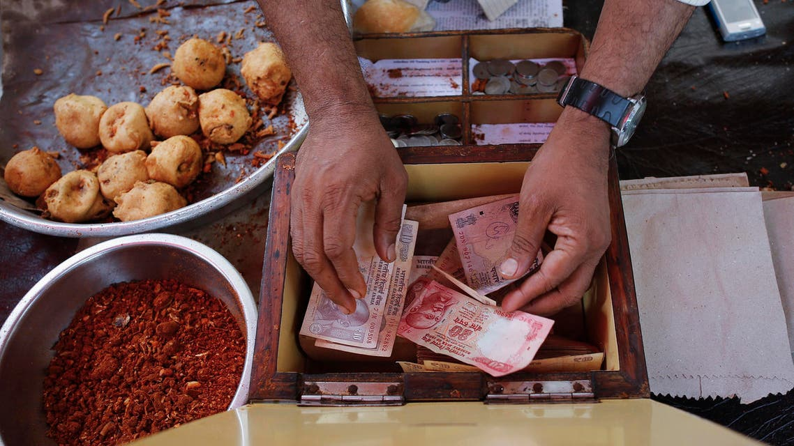 A streetside restaurant owner keeps money received from a customer in Mumbai December 5, 2013. (Reuters)