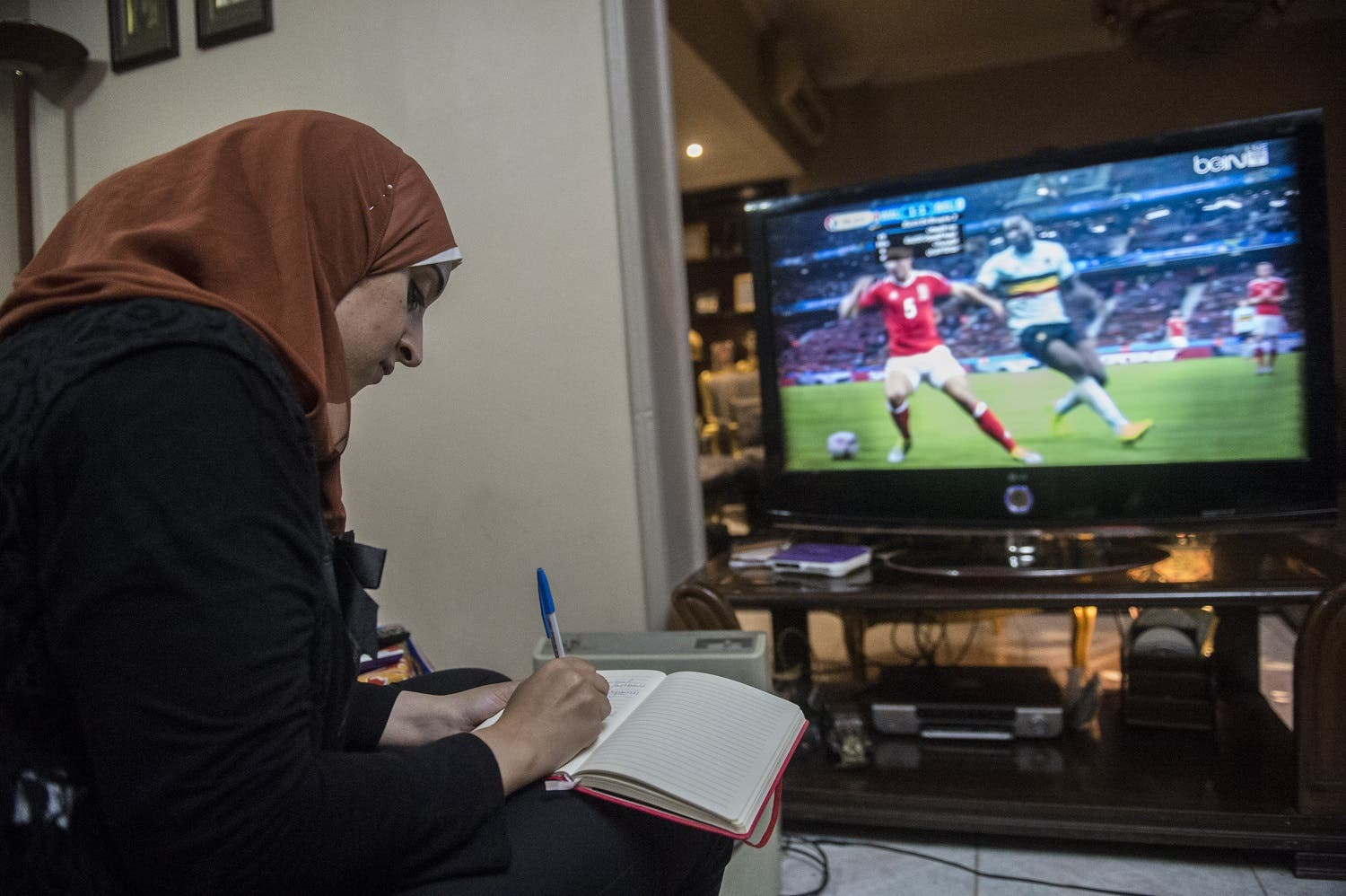 Football analyst Manar Sarhan takes notes while watching the Euro 2016 quarter-final between Wales and Belgium at her home in the Egyptian capital Cairo. (AFP)