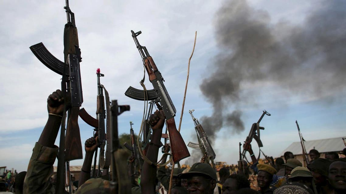 Rebel fighters hold up their rifles as they walk in front of a bushfire in a rebel-controlled territory in Upper Nile State, South Sudan February 13, 2014. (Reuters)