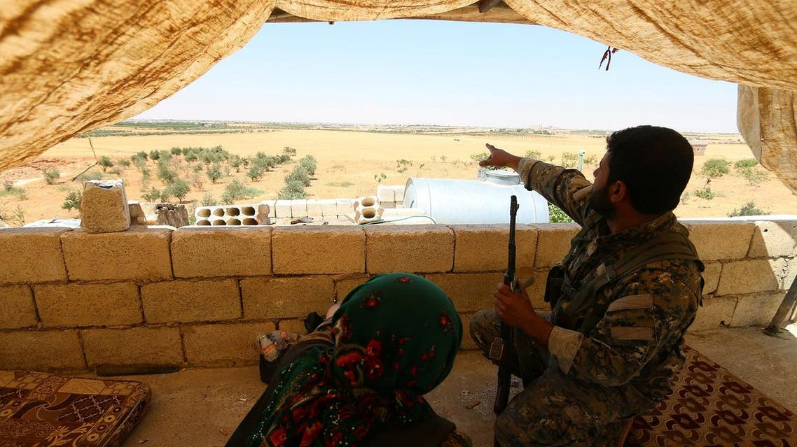 A fighter of the Syria Democratic Forces (SDF) points while sitting in a look out position in the western rural area of Manbij, in Aleppo Governorate, Syria, June 13, 2016. REUTERS