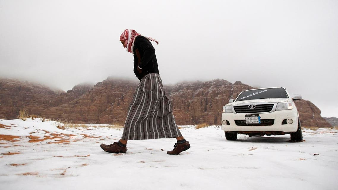 A man walks over snow after a snowstorm in the desert near Tabuk, northwest of Riyadh February 21, 2015. REUTERS