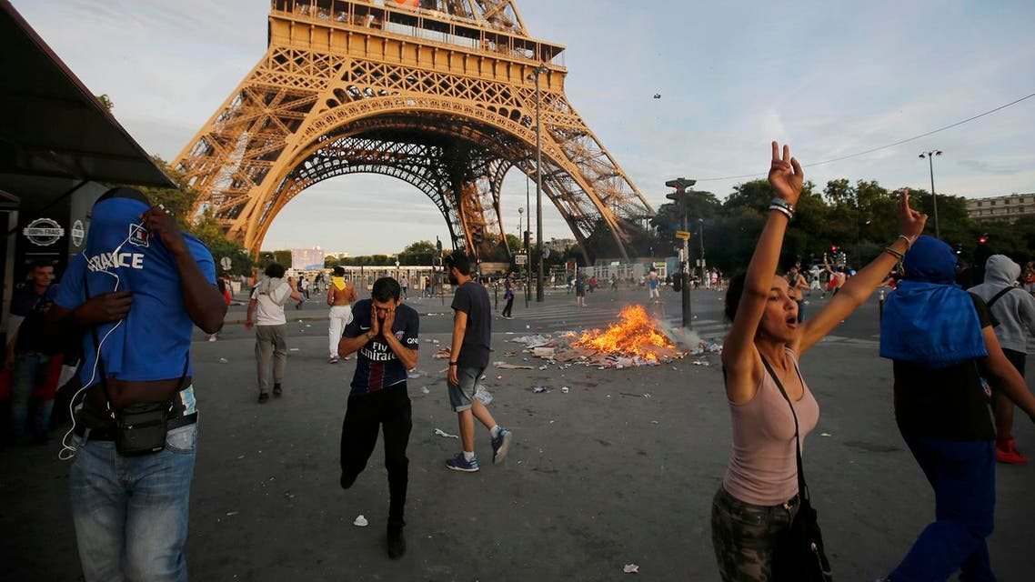 """Garbage burns during clashes near the Paris fan zone at the Eiffel Tower during the Portugal v France EURO 2016 final soccer match, in Paris, France, July 10, 2016. French police fired tear gas to disperse dozens of people trying to enter the """"fan zone"""" at the foot of the Eiffel Tower to watch the final of the Euro 2016 soccer tournament on Sunday evening, to prevent overcrowding. REUTERS/Stephane Mahe"""