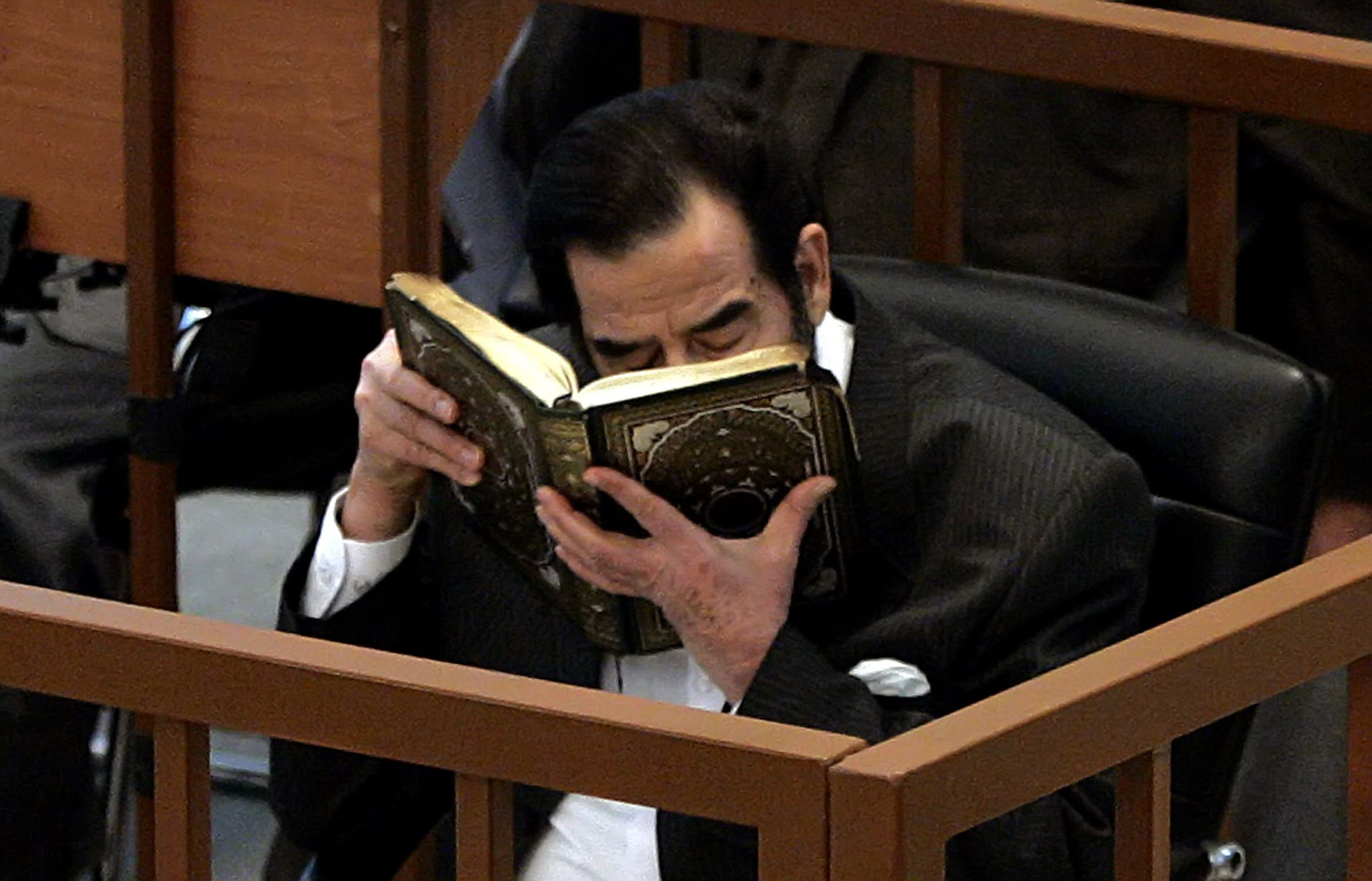Former Iraqi President Saddam Hussein kisses the Holy Koran moments after addressing the court during his trial in Baghdad, 06 December, 2005. (AFP)